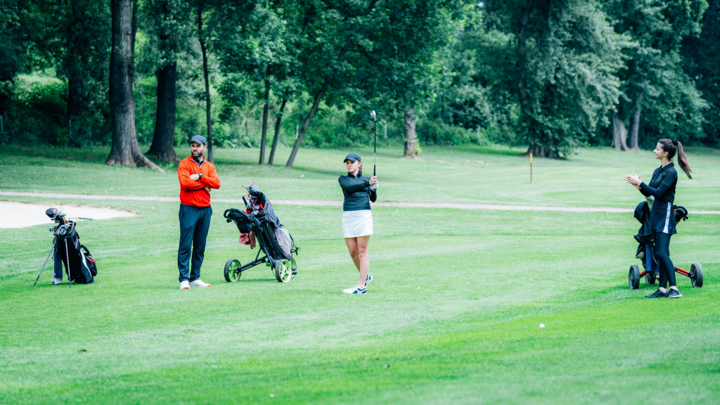 Golf training. Two young ladies with golf instructor having a lesson on a golf course