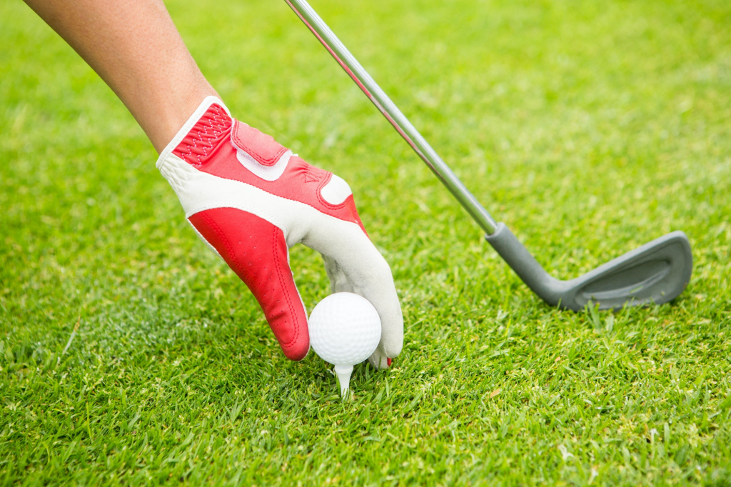 Golfer placing golf ball on tee at the golf course