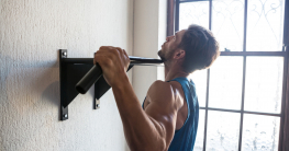 Side view of male athlete practicing pull ups on bar by window